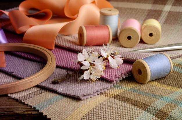 Naaibenodigdheden, naalden, vintage schaar op het kleurrijke jute textiel Premium Foto