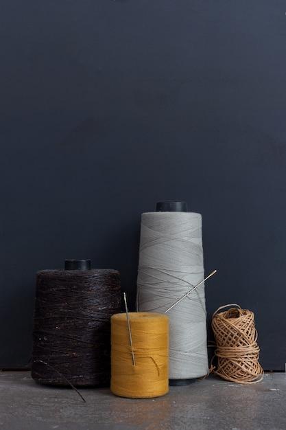 Naaibenodigdheden. schaar, naald, vingerhoed op zwart Premium Foto