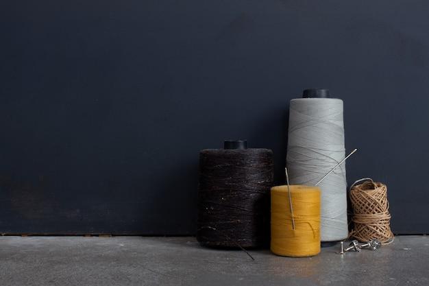 Naaibenodigdheden. schaar, naald, vingerhoed op zwarte achtergrond Premium Foto