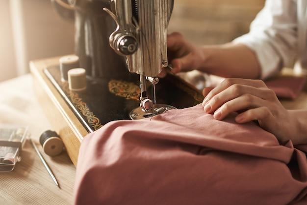 Naaien houdt mijn geest ontspannen. bebouwd schot van vrouwelijke kleermaker die aan nieuw project werken, die kleren met naaimachine in workshop maken, die bezig zijn. jonge ontwerper die haar ideeën laat uitkomen Gratis Foto