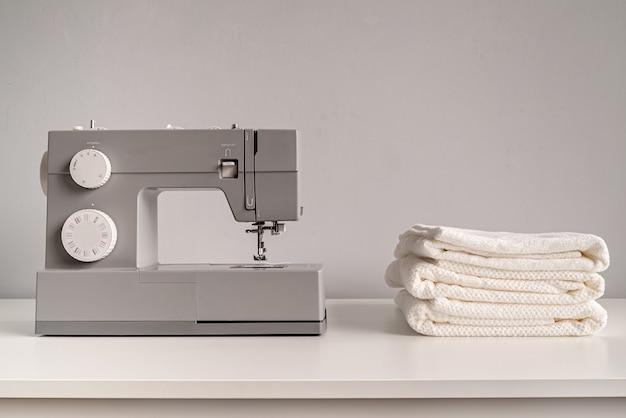 Naaimachine met witte handdoeken op kleermakerslijst Premium Foto