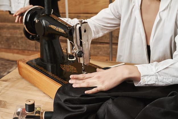 Naaister bezig met nieuw project. vrouwelijk riool dat met stof werkt, modieus kledingstuk met naaimachine in haar werkplaats creëert, geconcentreerd op naald om naad er netjes uit te laten zien Gratis Foto