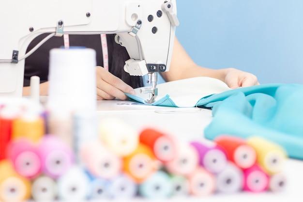 Naaister naaien op een naaimachine close-up. een set items voor handwerk: draden, naalden, pinnen, schaar, meetlint, enz. Premium Foto