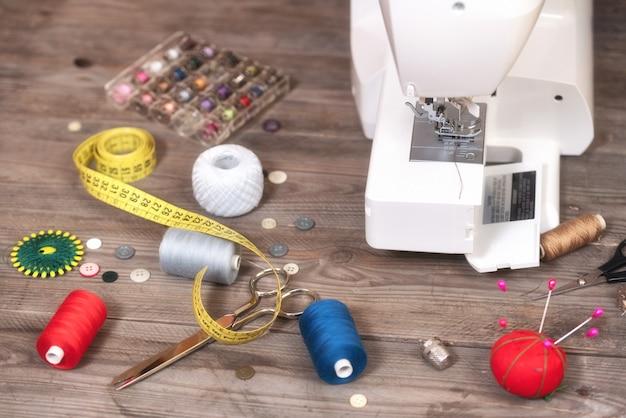Naaister of kleermakerachtergrond met naaiende hulpmiddelen, kleurrijke draden, naaimachine en toebehoren. Premium Foto
