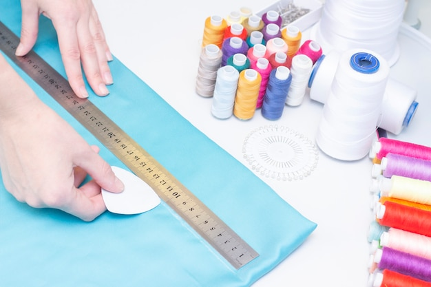Naaister omcirkelt het patroon op de stoffen close-up. een set items voor handwerken: draden, naalden, spelden, schaar, meetlint, enz. Premium Foto
