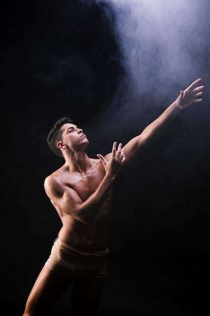 Naakte atletische mens die en handen opheft heft dichtbij rook op Gratis Foto