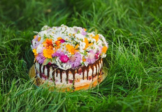 Naakte cake versierd met bloemen op gras. Premium Foto