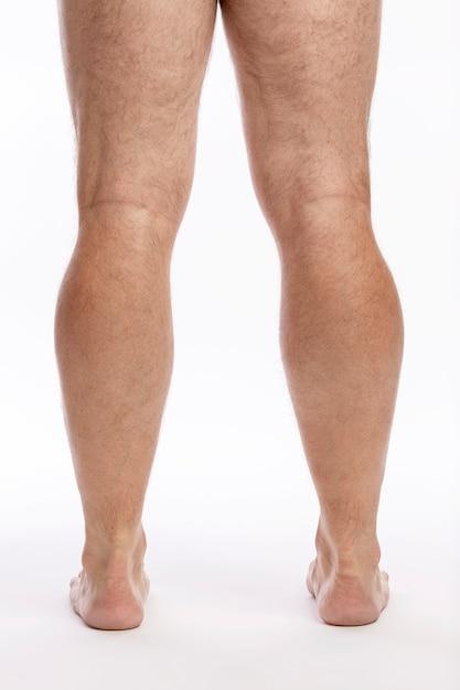 Naakte harige mannelijke benen op een witte muur. detailopname. Premium Foto