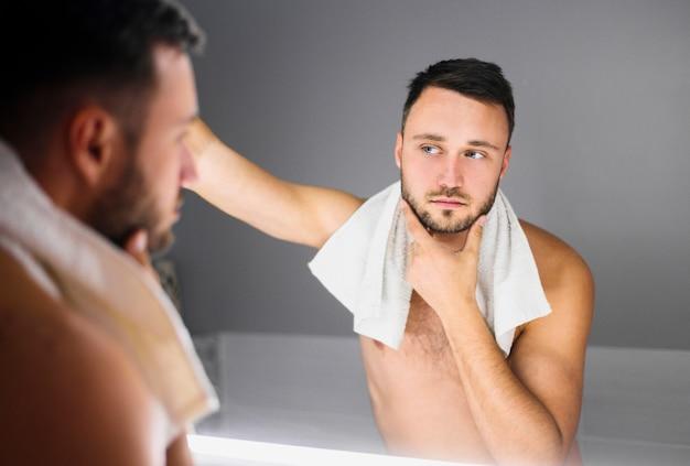 Naakte man met badhanddoek om zijn nek Gratis Foto