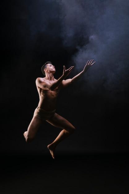 Naakte mens die en handen springt opheft tegen zwarte achtergrond Gratis Foto