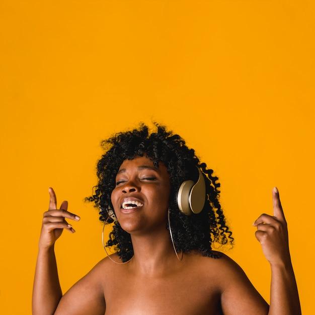 Naakte zwarte jonge vrouw zingen in de hoofdtelefoon in de studio Gratis Foto