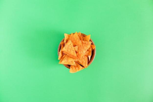 Nachos maïs chips in een houten kom op groen Premium Foto