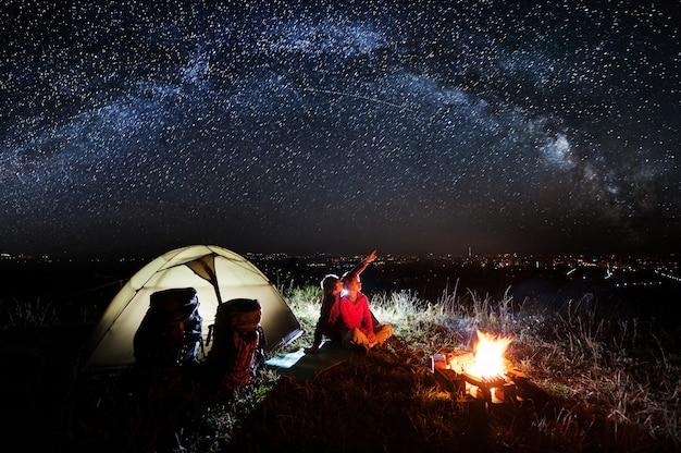 Nacht kamperen in de buurt van de stad in de buurt van kampvuur en tent Premium Foto