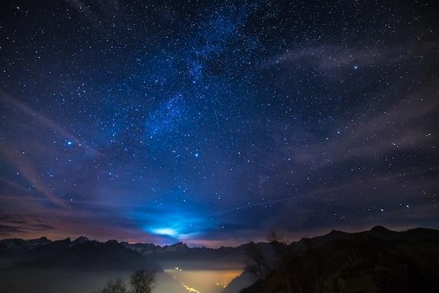Nacht op de alpen onder sterrenhemel en maanlichtachtergrond Premium Foto