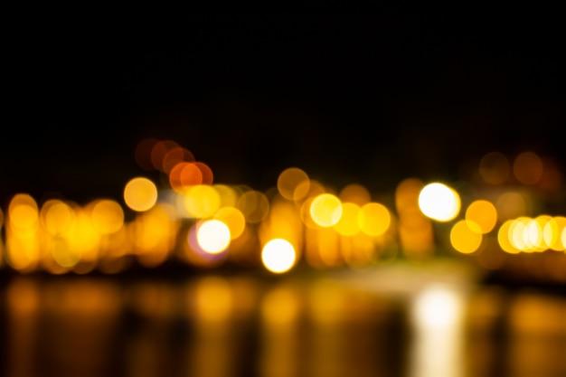 Nacht schemering wazig licht goud bokeh nadenken over de zee oppervlaktewater abstracte achtergrond Premium Foto