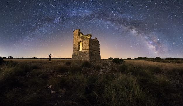 Nachtlandschap met de melkweg over een oud kasteel Premium Foto