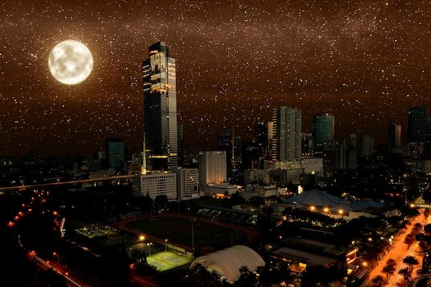 Nachtscène van moderne stad met gloeiende lichten en sterren Premium Foto