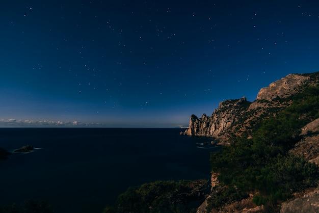 Nachtschot van sterrige donkerblauwe hemel, bergen en overzees in dorp van novy svet in de krim Premium Foto