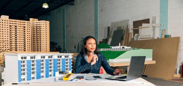 Nadenkend afrikaans-amerikaanse dame met laptop en model van gebouw Gratis Foto