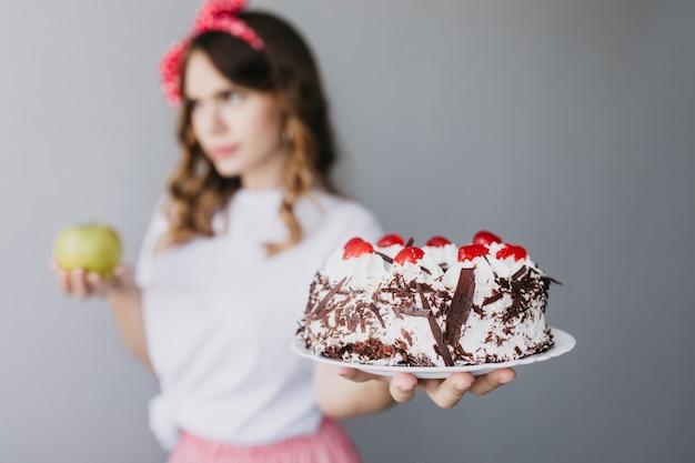 Nadenkend bevallig meisje chocoladetaart houden en na te denken over dieet. vervagen portret van brunette vrouw met romige taart op voorgrond. Gratis Foto