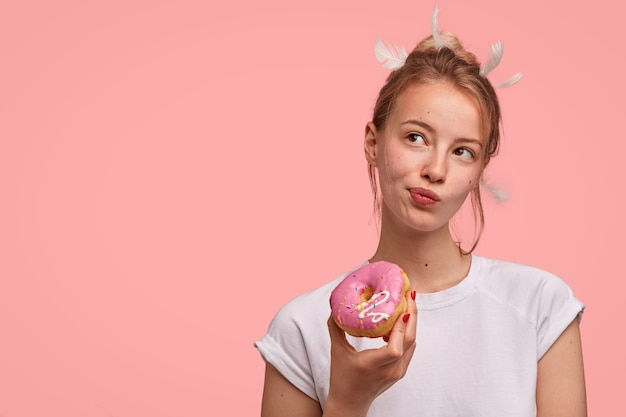 Nadenkend blanke vrouw met veren op het hoofd, kijkt bedachtzaam opzij, houdt heerlijke zoete donut vast, gekleed in een casual wit t-shirt, staat tegen roze muur met lege ruimte voor tekst Gratis Foto