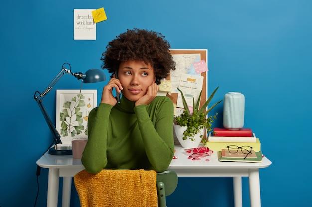 Nadenkend curly haired studente belt groepsgenoot via smartphone, zit aan stoel in eigen studeerkamer, tafel met bureaulamp en blocnotes, plaknotities op muur met schriftelijke informatie Gratis Foto