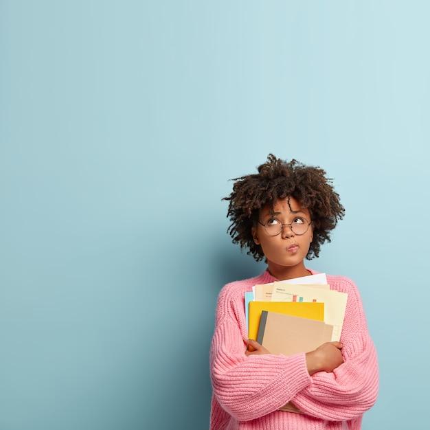 Nadenkend donkere student houdt papieren en leerboeken Gratis Foto