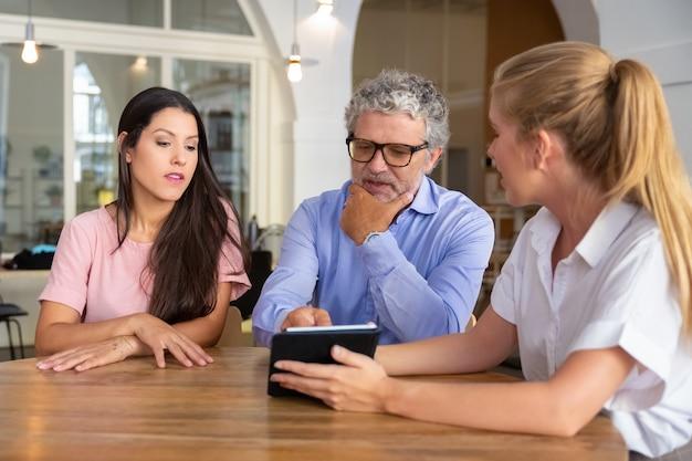 Nadenkend ernstige jonge vrouw en volwassen man ontmoeting met vrouwelijke professional, kijken en bespreken van inhoud op tablet Gratis Foto