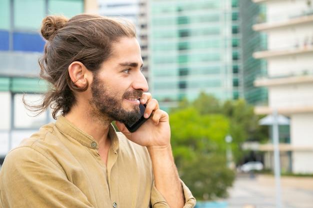 Nadenkend gelukkig hipster man praten op cel Gratis Foto