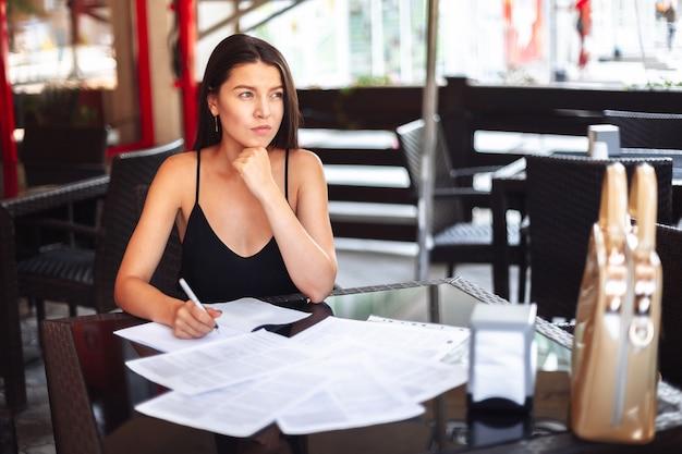 Nadenkend jong meisje zakenvrouw student zitten in een cafe op straat met documenten op tafel. Premium Foto