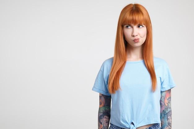 Nadenkend jonge mooie roodharige getatoeëerde vrouw kijkt ernstig opzij en draait haar mond terwijl ze tegen een witte achtergrond in een blauw t-shirt staat Gratis Foto