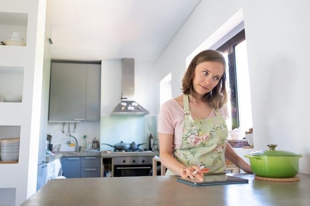 Nadenkend jonge vrouw internet raadplegen tijdens het koken in haar keuken, met behulp van tablet in de buurt van grote pan op teller. vooraanzicht. thuis koken en online kookboekconcept Gratis Foto