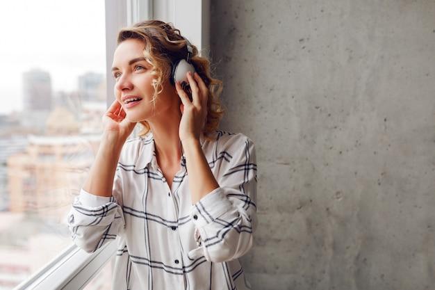 Nadenkend lachende vrouw luisteren muziek door oortelefoons, poseren in de buurt van venster. modern interieur. Gratis Foto