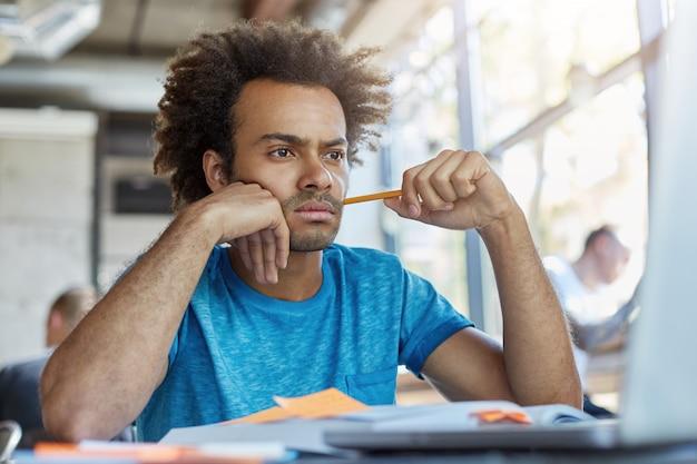 Nadenkend mannelijke freelancer achter coffeeshop kijken met ernstige uitdrukking in laptop werken met papieren proberen zijn best te doen tijdens het werken. donkerhuidige student met potlood bezig Gratis Foto