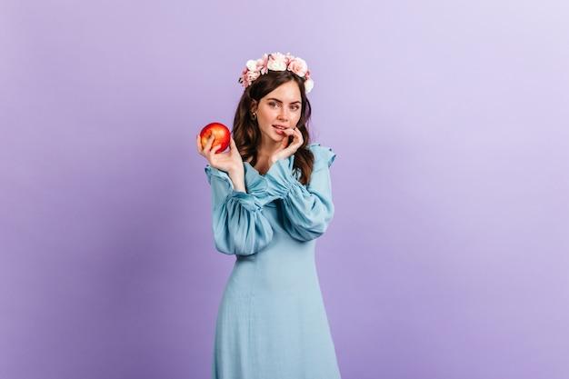 Nadenkend meisje dat sluw kijkt, smakelijke appel houdt. portret van model met kroon van bloemen op lila muur. Gratis Foto