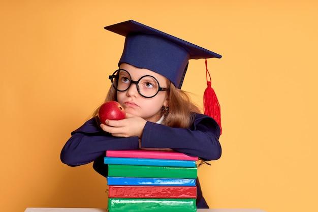 Nadenkend meisje die in glazen en afstuderenkleren denken terwijl leg op de kleurrijke boeken Premium Foto