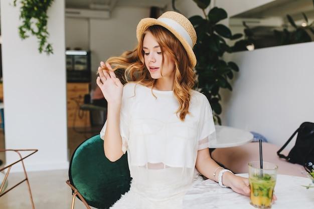 Nadenkend meisje in trendy witte kleding spelen met glanzende krullen tijdens het wachten vriendje in restaurant Gratis Foto