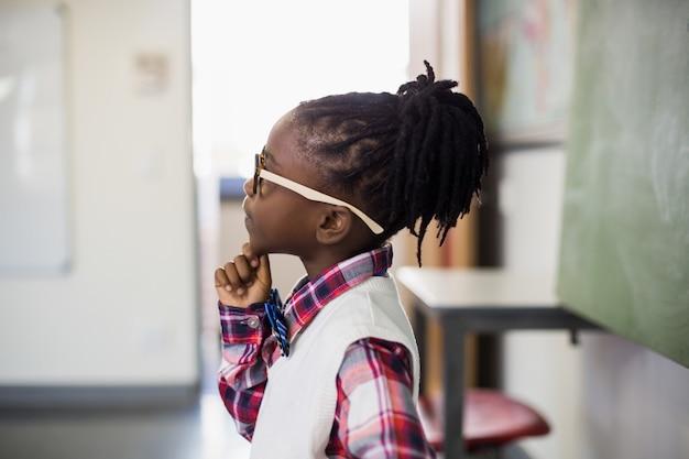 Nadenkend schoolmeisje dat zich met hand op kin in klaslokaal bevindt Premium Foto