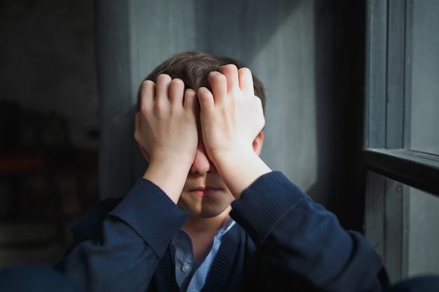 Nadenkend trieste tienerjongen zit bij het raam en sluit zijn gezicht met zijn handen Premium Foto