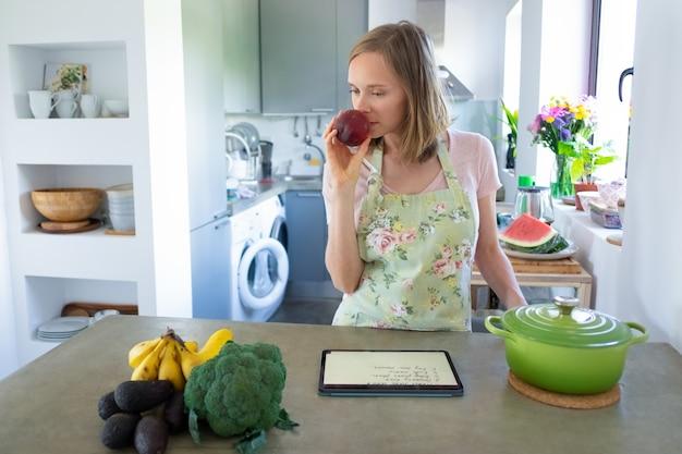 Nadenkend vrouw fruit ruiken tijdens het koken in haar keuken, met behulp van tablet in de buurt van steelpan en verse groenten op teller. vooraanzicht. thuis koken en gezond eten concept Gratis Foto