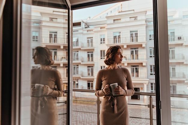 Nadenkend vrouw in bruine jurk cappuccino drinken. portret van een geweldig goed uitziend meisje met een kopje koffie staande in de buurt van balkon. Gratis Foto