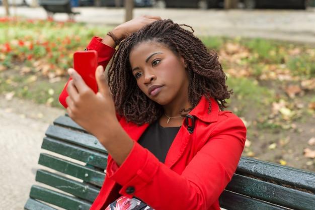 Nadenkend vrouw met behulp van smartphone in park Gratis Foto