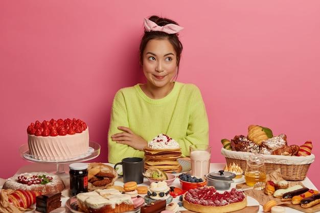 Nadenkend vrouwelijke zoetekauw eet graag zoete desserts, poseert aan tafel vol lekkere taarten, pannenkoeken, koekjes, drinkt koffie of melk, omringd door junkfood met veel suiker. Gratis Foto