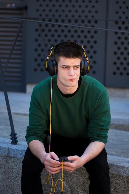 Nadenkende fronsende kerel met hoofdtelefoons Gratis Foto