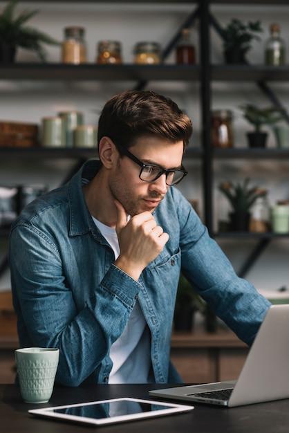 Nadenkende jonge mens die digitale tablet op keukenteller bekijken Gratis Foto