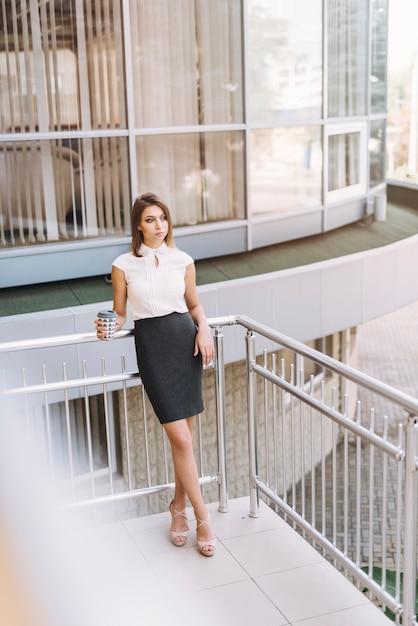 Nadenkende jonge onderneemster die meeneemkoffiekop houden die zich in het balkon bevinden Gratis Foto