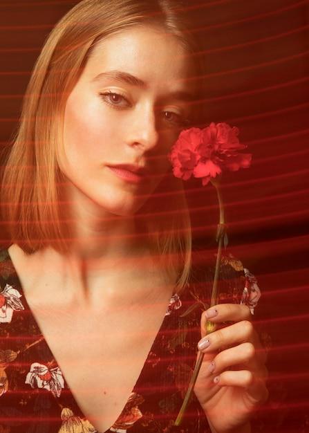 Nadenkende jonge vrouw met rode anjer Gratis Foto