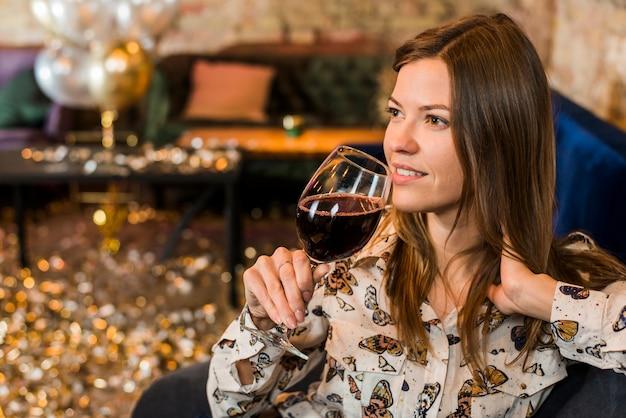 Nadenkende jonge vrouw met wijnglas in bar Gratis Foto