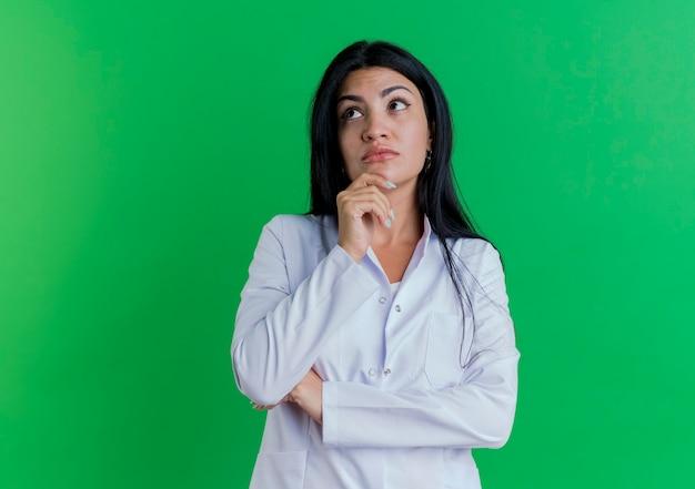 Nadenkende jonge vrouwelijke arts die medisch kleed draagt dat kant bekijkt wat betreft kin Gratis Foto