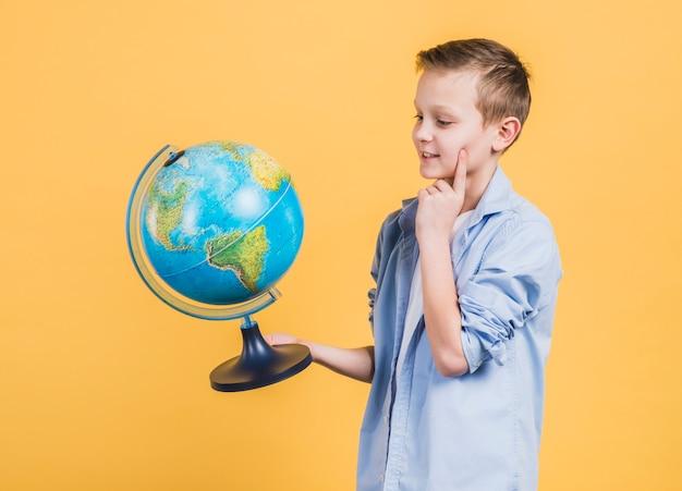 Nadenkende jongen die dichtbije bol kijkt die zich tegen gele achtergrond bevindt Gratis Foto